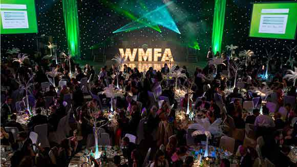 Large room with many people sitting at round tables and the letters WMFA at the front for the West Midlands Finance Awards'