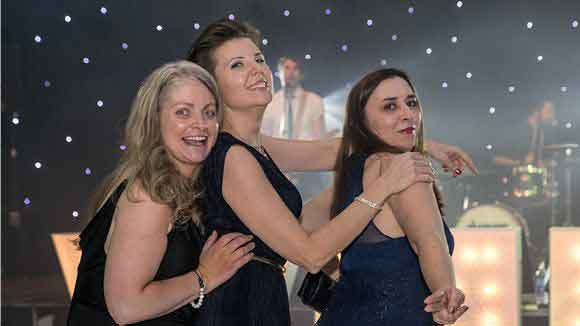 Three female finance professionals enjoying themselves on the dance floor at the Finance Awards