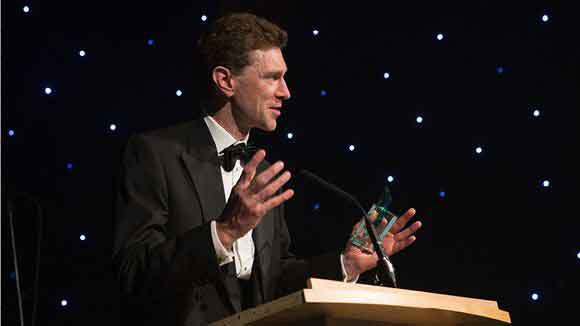 Male accepting an award at the finance awards and giving a speech