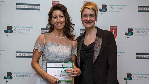 Two females in front of the award partners back drop holding an award and certificate