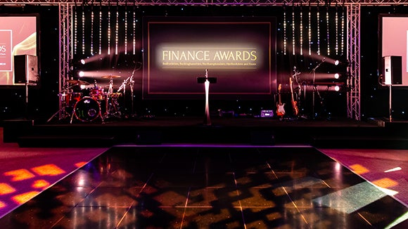 The Finance Awards stage with the presentation in the background and the word award in front of the stage