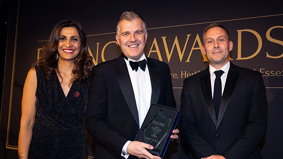 Male finance professional accepting Business of the Year Award from another male