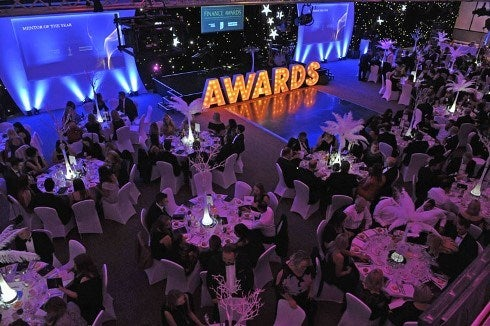 Large room with many people sitting at round tables and the word awards at the front for the Finance Awards
