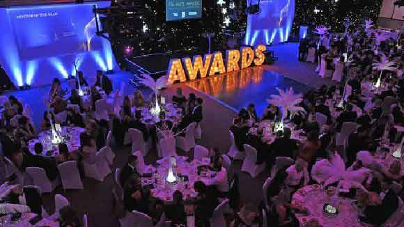 Large room with many people sitting at round tables and the letters AWARDS at the front for the finance awards