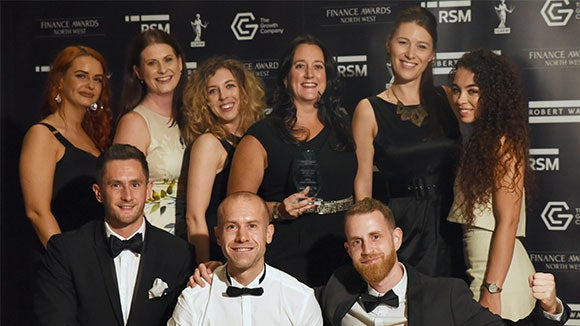 finance awards winners in black tie attire and dresses in front of the sponsors marquee posing for photo