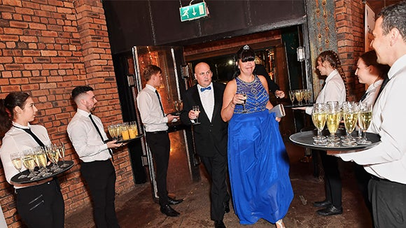 woman in blue dress walking through waiters with champage at the north west pa of the year awards