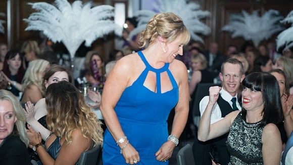 woman in blue dress celebrating her win at the Manchester PA Awards