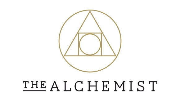 the alchemist logo black with gold triangle shape