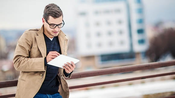 man in brown jacket looking at skill shortage data outside on ipad