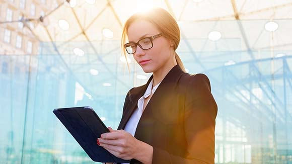 woman in suit on tablet looking at the most important finance qualifications