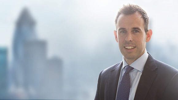 Neil Morgan, Associate Director at Robert Walters, against faded city background