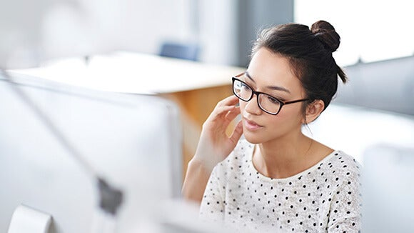 woman in white polka dotted shirt sitting at computer with glasses on researching women in workplace initiatives