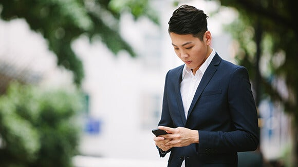 HR professional looks for new job on mobile phone in city