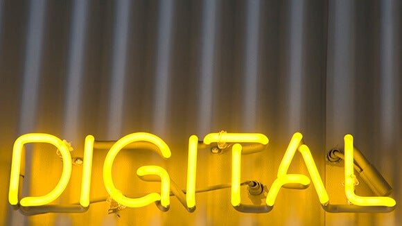 Neon yellow lights lighting up a sign saying digital