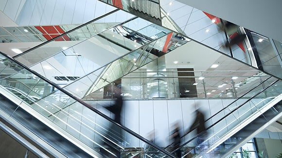 Four overlapping mirrored escalators in a banking office with banking professionals