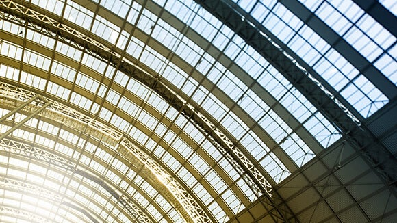 train station building roof with glass panels and sun shining through