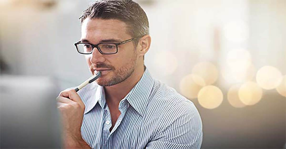 man wearing glasses making changes to LinkedIn profile online