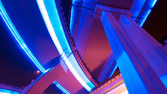 neon blue and pink highway shot at night from underneath looking up