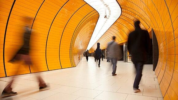 Commuters go to work in an orange tunnel