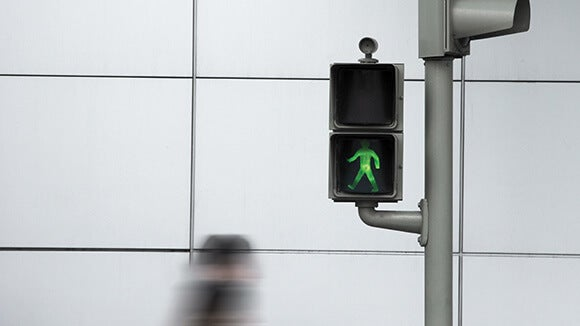 A Man Walking Past Green Road Light With White Wall In The Background