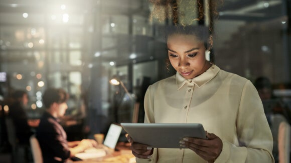 woman on a tablet looking at ways to attract diverse talent
