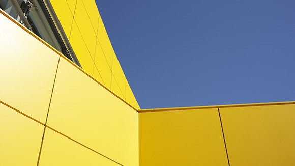 Side of a yellow building at an angle with blue sky in the background