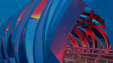 side of blue, red and yellow sphere shaped bridge at night