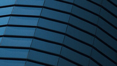 blue side of a rounded building with panels