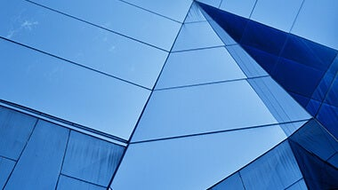 blue glass building with angular walls