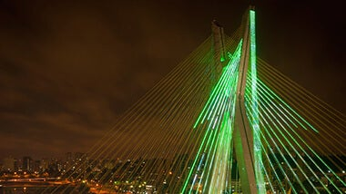 neon bridge with green lights behind view our latest opportunities