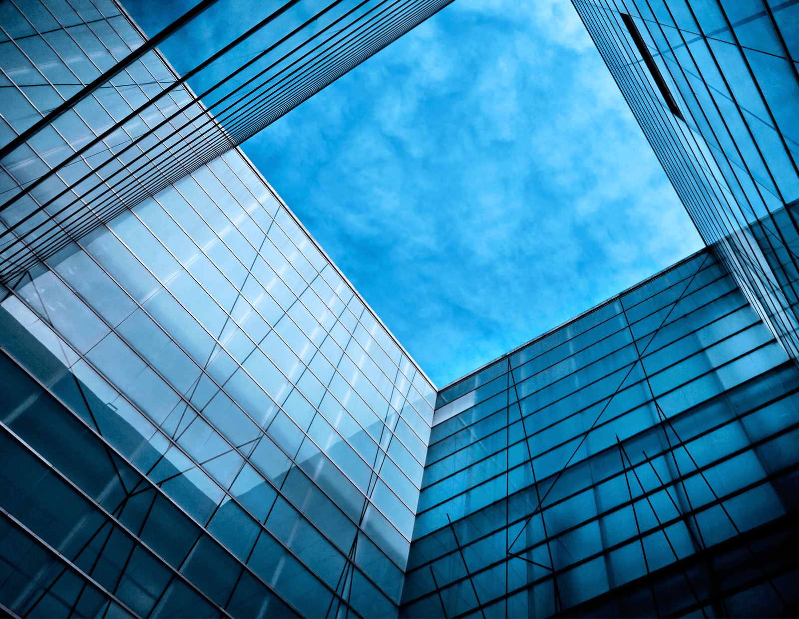 glass building with square of blue sky hero image