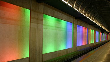 colour panel building with multiple colours on back wall behind train line